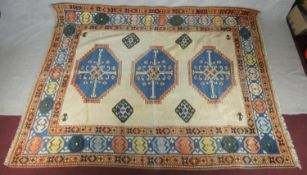 A Heriz carpet with triple hooked lozenge medallions on a fawn ground within multiple stylised