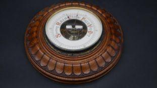 A C.1900 oak cased barometer with well carved sunburst decoration. D.23.5cm