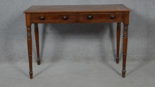 A 19th century mahogany writing table fitted with a pair of frieze drawers on ring turned tapering