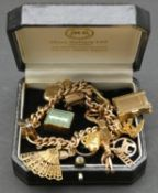 A vintage solid curb link 9ct gold charm bracelet with fifteen 9ct yellow gold charms. The charms