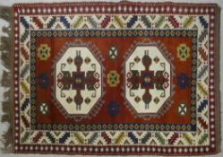 A Turkish Kars rug with double hooked medallions on a burgundy ground within stylised serrated