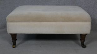 A 19th century style upholstered footstool on turned tapering supports. H.36 L.80 W.59cm