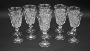 A set of eleven engraved and cut crystal wine glasses with star design and faceted stems. H.17.5cm