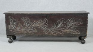 An 18th century oak plank coffer with foliate carved front on bun feet. H.49.5 W.126 D.34.5cm