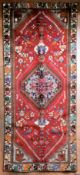 A Persian Kashkai with central hooked lozenge medallion on madder field decorated with birds and