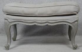 A painted Louis XV style footstool in double piped calico upholstery on carved scrolling cabriole