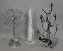 A glass table lamp in the shape of a candle flame and two other metal table lamps. H.65cm (Tallest)