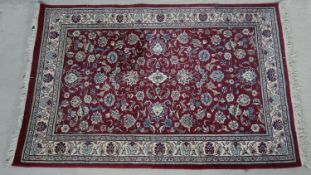 A Persian style rug with scrolling floral decoration across the burgundy field within naturalistic