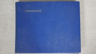 An album containing fifty three pages with fifty five chocolate wrappers and packaging for mainly