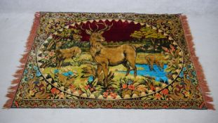A vintage red velvet tapestry with stags and deers in a woodland clearing by a lake. H.170 W.120cm