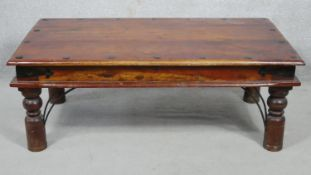 An Indian hardwood and metal bound low table on circular section turned supports. H.41 L.110.5 W.
