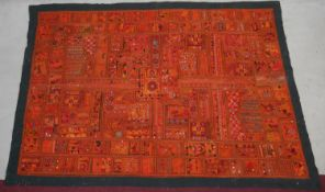 An Eastern bed covering or wall hanging with patchwork style design inset with mirrored discs. L.218