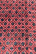 A modern rug with all over repeating diamond pattern on a rouge ground. L.190 W.125cm