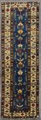 A Kazak style runner with repeating serrated palmette motifs on a sapphire ground contained by