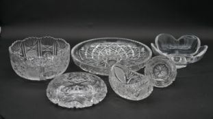 A collection of crystal items to include two cut crystal bowls, a boat shaped dish, two ash trays