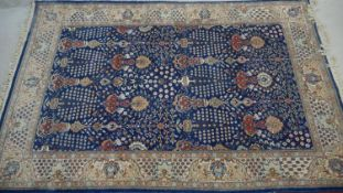 An Eastern carpet with repeating medallions and floral motifs across a sapphire ground within