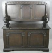 A mid century oak Jacobean style monk's bench with sliding action metamorphic table top on hinged