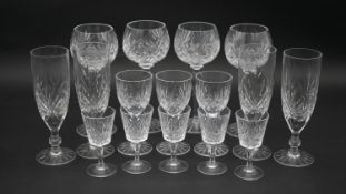 A collection of sixteen cut crystal glasses. Including a set of four foliate design wine glasses,