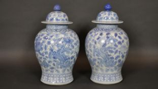 A pair of Chinese blue and white lidded temple jars with all over foliate, lotus flower and dragon