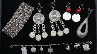 A collection of silver jewellery. Including an Israeli silver charm bracelet, silver coin earrings a