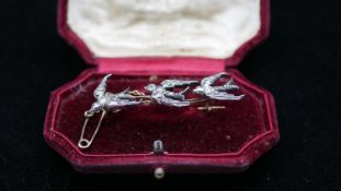 An antique silver and yellow metal diamond brooch with three swallows in a red velvet antique box.