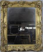 A 19th century carved giltwood and gesso wall mirror with scrolling Rococo frame and original plate.