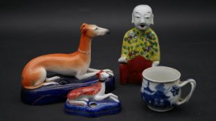 A Staffordhire figure of a seated greyhound, a similar figure, a seated Chinese male figure and a