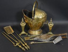 A 19th century embossed brass helmet form coal bucket and a set of three 19th century fire tools