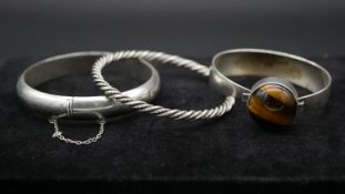 Three silver bangles. Including a Georg Jensen solid bangle with a twisted rope design, stamped with