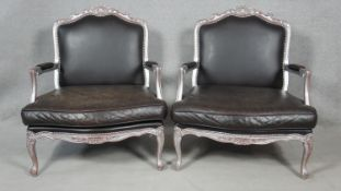A pair of Louis XV style armchairs in carved silvered distressed frames in black leather