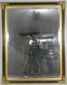 A large wall mirror with bevelled plate in ebonised and gilt floral frame. H.140 W.110cm
