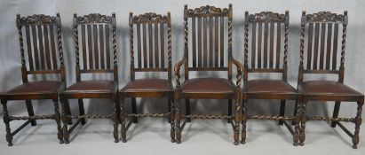 A set of six Carolean style oak dining chairs with carved back rails above drop in seats on