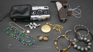 A collection of costume jewellery, a vintage Rollei 35 camera with case and other items. H.7 L.10.