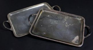 A silver plated twin handled serving tray with gadrooned edging along with a similar example. H.48