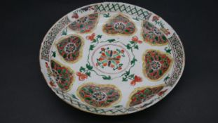 A Kangxi style Chinese Famille Rose porcelain hand glazed plate with stylized floral and foliate