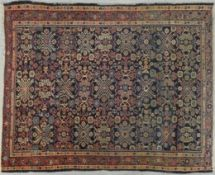 A Heriz style rug with all over repeating floral motifs on a deep blue ground within stylised