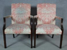 A pair of Georgian style mahogany framed open armchairs in blush floral upholstery. H.95 W.65 D.60cm