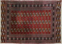 A Bokhara style rug with repeating gul motifs on a madder ground contained within stylised