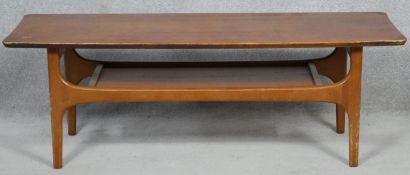 A mid century vintage teak coffee table on shaped supports united by undertier. H.40 L.116.5 W.41cm