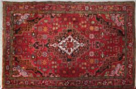 A Shirvan rug with central pole medallion on burgundy field contained by stylised floral spandrels