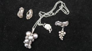 A Danish silver Georg Jensen suite of jewellery. Including pendant and chain, a pair of clip