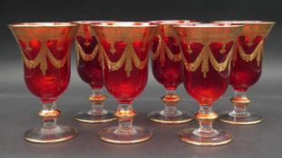 A set of six ruby glass goblets etched and with gold leaf decoration. H.16cm