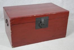 A Chinese red lacquered hardwood travelling trunk with twin metal carrying handles and lock. H.37