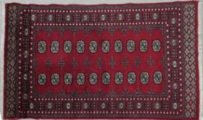 A Bokhara rug with repeating gul motifs on a deep red ground within stylised floral multiple