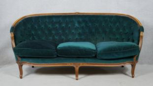 A French style carved beech three seater canape in deep buttoned velour upholstery on cabriole