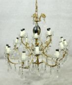 A gilt metal and glass sixteen branch two tier chandelier with cut crystal drops. D.72cm