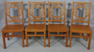 A set of four Chinese influenced hardwood dining chairs with panel seats on square section supports.