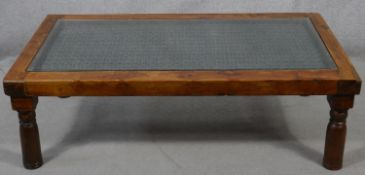 An Indian hardwood coffee table with plate glass on a metal lattice work inset top. H.41 L.132 W.