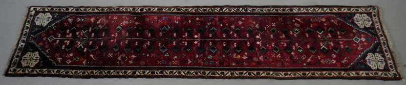 An Eastern runner with repeating stylised floral design on a madder field contained within