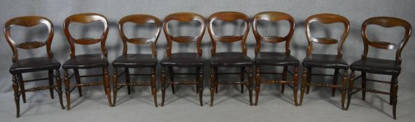 A set of eight Victorian carved mahogany balloon back chairs on swept turned stretchered supports.